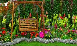 Деревянный стул качания в тропическом саде Стоковые Фотографии RF