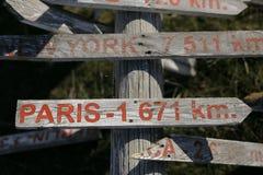 Деревянный указатель на земном показе которого путь Париж и новое Yourk Стоковое фото RF