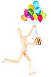 Деревянный думмичный держа подарок и воздушные шары летая Стоковое фото RF