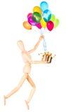 Деревянный думмичный держа подарок и воздушные шары летая Стоковые Изображения RF