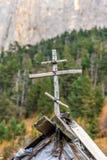 Деревянный христианский крест на крыше туристской хаты как символ защиты на скалистой предпосылке горного пика на сельской местно стоковое изображение