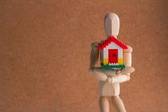 Деревянный человек держа домашнюю модель Концепция займа Стоковое фото RF