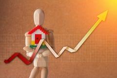 Деревянный человек держа домашнюю модель с анализом диаграммы роста jpg Стоковое Изображение