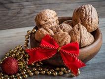 Деревянный шар вполне грецких орехов, красного смычка, орнамента золота и золотой цепи рождества Стоковые Фото