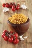 Деревянный шар вполне сухих макаронных изделий с томатами вишни и гвоздичными деревьями чеснока на деревянном столе стоковое изображение