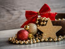 Деревянный шар с цепью жемчуга рождества золотой, орнаментом яркого блеска красного цвета и золота и золотой звездой с красным см Стоковое Изображение