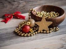 Деревянный шар с цепью жемчуга рождества золотой, орнаментом яркого блеска красного цвета и золота и золотой звездой с красным см Стоковое фото RF