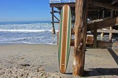 Деревянный surfboard против пристани пляжа Калифорнии Стоковая Фотография RF