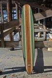 Деревянный surfboard против пристани пляжа Калифорнии Стоковая Фотография