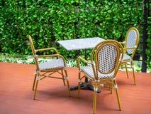 3 деревянных белых винтажных стуль с белой мраморной таблицей на красном поле на зеленой предпосылке завода плюща стоковые изображения rf