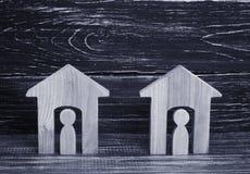 2 деревянных дома с людьми на черной предпосылке Концепция района, своих соседей Хорош-соседские отношения Стоковое Изображение RF
