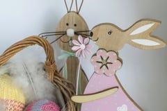 2 деревянных зайчика пасхи около плетеной корзины с 2 вязали яичка крючком перед яркой предпосылкой Стоковая Фотография