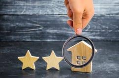 2 деревянных звезды и дом Гостиница или ресторан 2 звезд Обзор критика Гарантированное качество обслуживания и уровень обслуживан стоковое фото