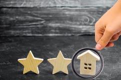 2 деревянных звезды и дом Гостиница или ресторан 2 звезд Обзор критика Гарантированное качество обслуживания и уровень обслуживан стоковые изображения