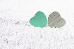 2 деревянных зеленых и серых сердца на белом искусственном снеге Стоковое Фото