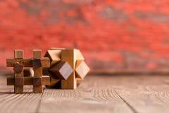 2 деревянных куба головоломки на деревянной предпосылке Стоковое Изображение