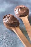 2 деревянных ложки сливк шоколада Стоковые Изображения RF