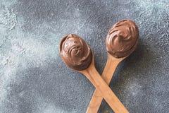 2 деревянных ложки сливк шоколада Стоковое Изображение RF