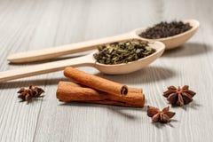 2 деревянных ложки с сухими листьями зеленого и черного чая, cinnam Стоковые Фото