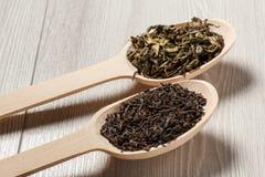 2 деревянных ложки с сухими листьями черного и зеленого чая Стоковая Фотография RF