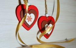 2 деревянных пестротканых сердца с silk лентой на bac света Стоковое Фото