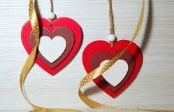 2 деревянных пестротканых сердца с silk лентой на bac света Стоковые Фото