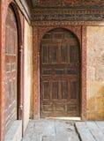 2 деревянных постаретых богато украшенных сводчатых перпендикулярных двери на каменных стенах кирпичей Стоковые Изображения RF