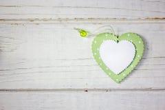2 деревянных сердца - белого и зеленого над деревянной предпосылкой Стоковая Фотография