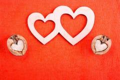 2 деревянных сердца и грецкого ореха 2 в форме сердца лежат дальше Стоковые Фото