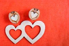 2 деревянных сердца и грецкого ореха 2 в форме сердца лежат дальше Стоковое фото RF