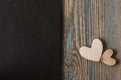 2 деревянных сердца помещенного славно на винтажной предпосылке Стоковая Фотография RF