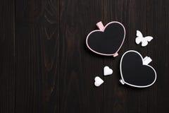 2 деревянных сердца с бабочкой на деревянной предпосылке Стоковое Изображение RF
