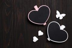 2 деревянных сердца с бабочкой на деревянной предпосылке Стоковая Фотография RF