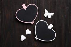 2 деревянных сердца с бабочкой на деревянной предпосылке Стоковая Фотография