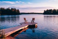 2 деревянных стуль на деревянной пристани обозревая озеро на заходе солнца Стоковые Фото