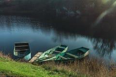 3 деревянных шлюпки мирно отдыхая на реке осени на Стоковая Фотография RF