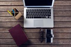 Держатель компьтер-книжки, дневника, зрелищ, камеры и ручки на деревянном столе Стоковое фото RF