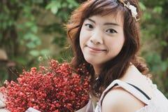 Держатель цветка довольно азиатской женщины детенышей нося и красный цвет держать стоковые фотографии rf