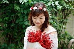 Держатель цветка довольно азиатской женщины детенышей нося и красный цвет держать стоковые изображения