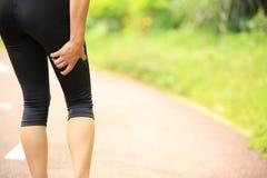 Держатель бегуна женщины ее ноги спорт раненые стоковая фотография rf