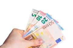 Держать бумажные деньги евро в руке на белой предпосылке Стоковые Изображения