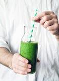 Держать зеленый smoothie Здоровый smoothie вытрезвителя в руках Стоковая Фотография RF