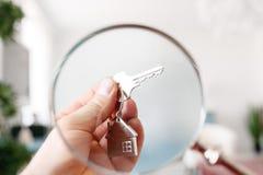 Держать ключи дома на доме сформировал крупный план keychain имущество принципиальной схемы реальное Стоковые Изображения RF