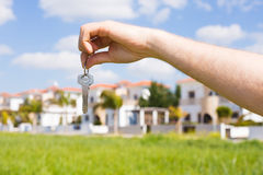 Держать ключи дома на доме сформировал крупный план keychain перед новым домом имущество принципиальной схемы реальное Стоковые Фото