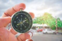 Держать компас на горе дерева и предпосылке моря расплывчатой Usin Стоковая Фотография