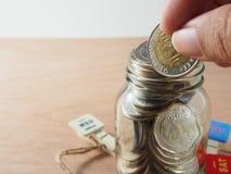 Держать монетку, деньги бата на стекле копилки Стоковое фото RF