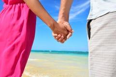 Держать пар новобрачных рук романтичных на пляже Стоковое Фото