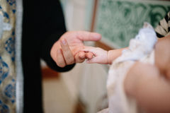 Держать руку младенца во время крестить Стоковое Изображение
