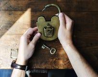 Держать рук открывает Padlock и пользуется ключом на деревянном столе Стоковое Фото