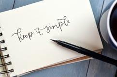 ДЕРЖИТЕ рук-lettered ИТ ПРОСТОЕ в блокноте Стоковые Изображения RF
